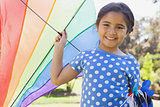 Happy young girl holding kite at park