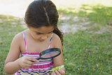 Girl examining a leaf with magnifying glass at park