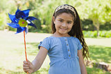 Cute little girl holding pinwheel at park