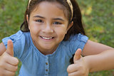 Young girl gesturing thumbs up at park