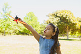 Girl playing with a toy plane at park