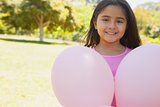 Portrait of a girl with pink balloons at park