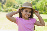 Young happy girl wearing hat in park