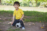 Portrait of a cute boy sitting on football at park