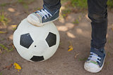 Low section of boy with leg on football at park