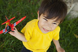 Young boy playing with a toy plane at park