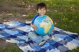 Cute young boy holding globe at park