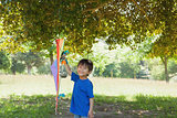 Happy young boy holding kite at park