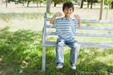 Happy young boy sitting on bench at park