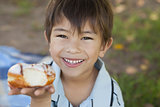 Happy young boy hyolding burger at park