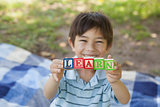 Happy boy holding block alphabets as 'learn' at park