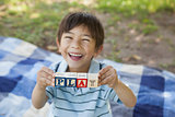 Happy boy holding block alphabets as 'play' at park
