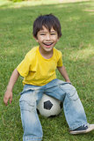 Cute little boy sitting on football at park
