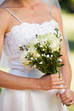 Mid section of a beautiful bride with bouquet in park