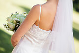 Mid section of a young beautiful bride with bouquet