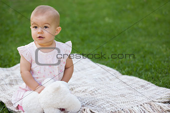 Baby with stuffed toy sitting on blanket at park