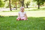 Happy cute baby sitting on grass at park