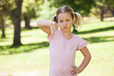 Displeased girl gesturing thumbs down at park