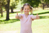 Smiling young girl gesturing thumbs up at park