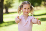 Smiling girl gesturing thumbs up at park