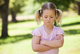 Sad young girl with arms crossed at park