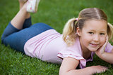 Smiling relaxed girl lying on grass at park