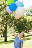 Young girl with colorful balloons at park