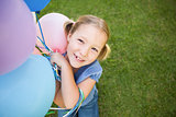 Portrait of a girl with colorful balloons at park