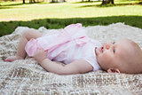 Side view of a cute baby lying on blanket at park