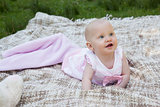 Cute baby lying on blanket at the park
