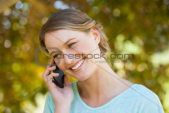 Beautiful woman using mobile phone in park