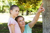 Mother pointing at something besides daughter at park
