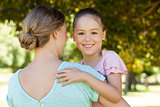 Smiling daughter embracing her mother at park
