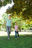 Happy mother and daughter walking at park