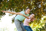 Portrait of mother and daughter with arms outstretched at park