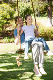 Happy mother and daughter sitting on swing at park