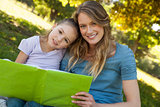 Happy mother and daughter reading a book at park