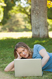 Relaxed young woman using laptop at park