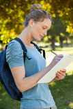 Beautiful young woman writing on clipboard at park