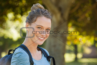 Beautiful young woman with backpack at park