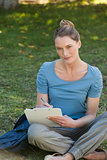 Relaxed young woman writing on clipboard at park