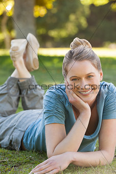 Beautiful relaxed woman lying on grass at park