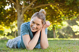 Beautiful relaxed young woman lying on grass at park