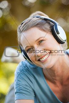 Beautiful young woman enjoying music in park