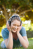 Beautiful relaxed woman enjoying music in park
