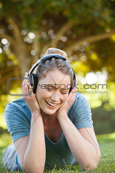 Beautiful relaxed woman enjoying music in park