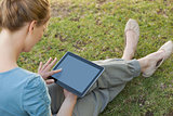 Relaxed young woman using digital tablet at park