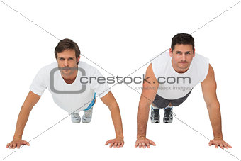 Portrait of two young men doing push ups