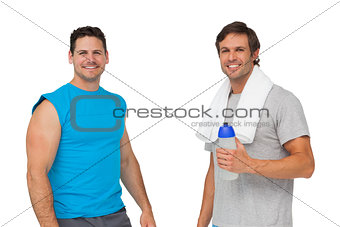 Portrait of two fit men with water bottle and towel