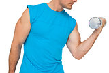 Close-up mid section of fit man exercising with dumbbell